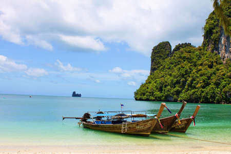 phi phi island:  Long tailboats by the shore at Hong Island, Krabi Thailand against beautiful clear blue sky
