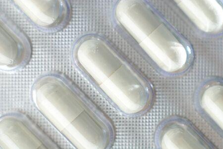 pilule: Cápsulas Rep en hojas, primer plano, aislado con la sombra