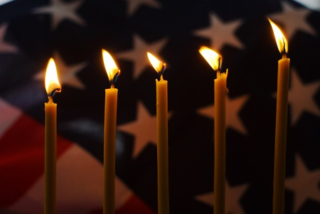 Lighted candle with an old American flag