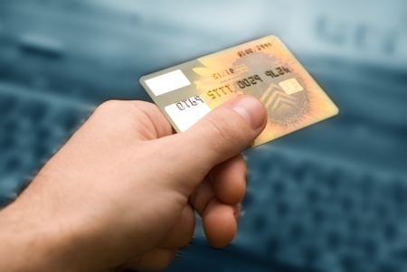 credit card in hand for purchases are in the internet