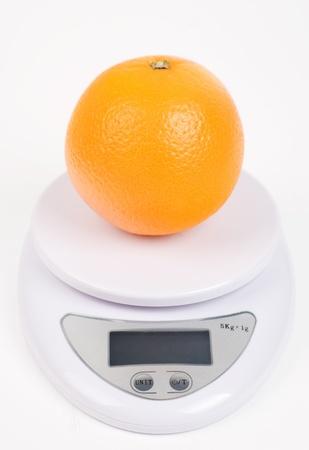 orange on digital scale isolated on white photo