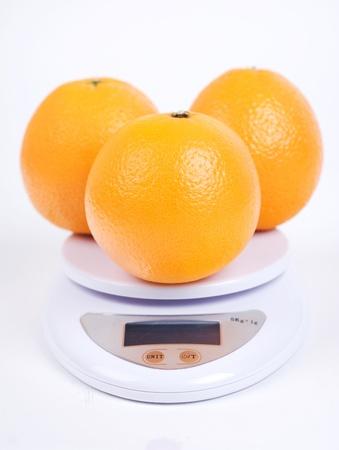 oranges on digital scale isolated on white photo
