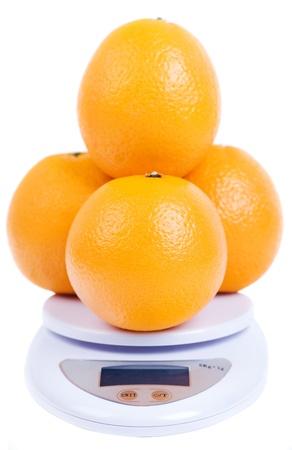 oranges on digital scale isolated on white Stock Photo - 13446681