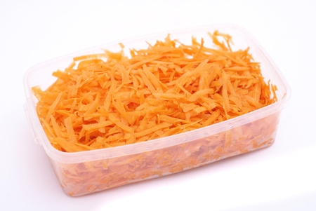 grated carrot in plastic container isolated on white photo