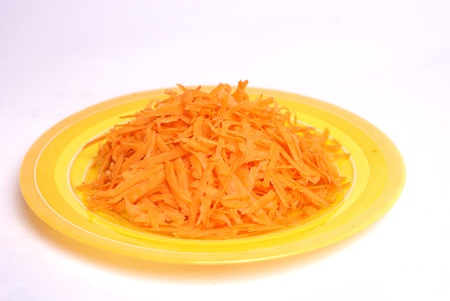 grated carrot on dish isolated on white photo