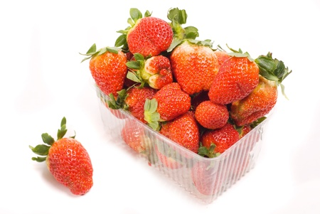 heap strawberry in plastic container isolated on white photo