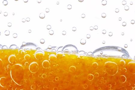 orange splash: peel of orange with bubbles mineral waters on white