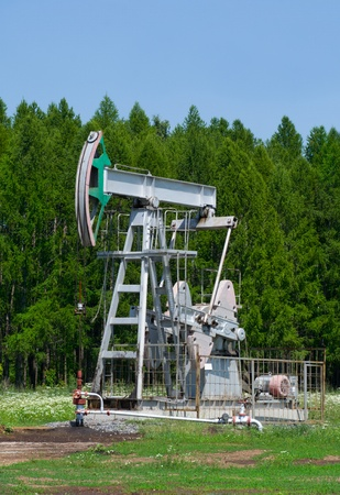 industrially: oil pump on a background the forest  Stock Photo