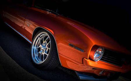 검은 배경과 크롬 바퀴에 오렌지 빈티지 아메리칸 클래식 자동차