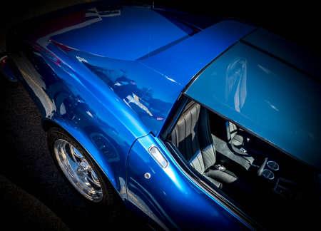 黒の背景にブルーアメリカンクラシックスポーツカー