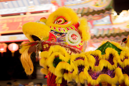 Acrobats are performing a lion and dragon dance with a well trained skill, danger but very exciting on February 12, 2014 in Yala, Thailand.