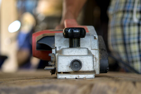 shove: A man is using an electric carpenters jack plane to shove a wood. Stock Photo