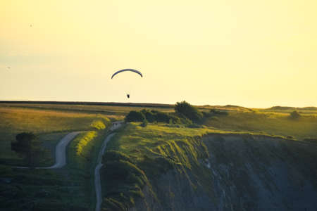 Rocky cliffs covered with green grass at sunset. A man practicing paragliding over them. Normandy, France.