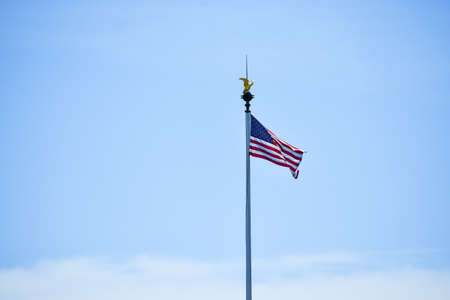 Isolated United States flag waving in the wind in a blue sky background. Copy space for text. 版權商用圖片