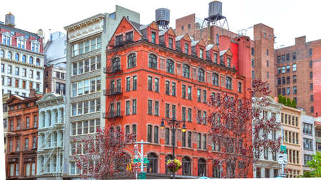 Colorful brick buildings, with windows and fire stairs. Water deposits on rooftops. NYC, USA