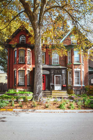 Red brick houses and mansard roofs with garden and tree in autumn. Gananoque, Canada. Stock Photo