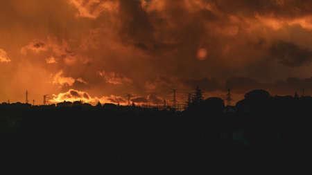 Dramatic orange cloudy sunset in the city, from the window of the train. Stock Photo