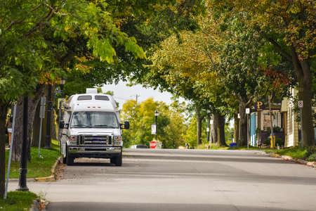 Van Lifestyle concept. Van parked in a street between trees in Autumn. Gananoque, Canada.