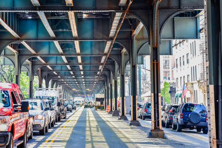 Bottom view of Elevated train track nyc. Traffic waiting in road in a sunny day. Travel and traffic concepts. Bronx, NYC, USA.