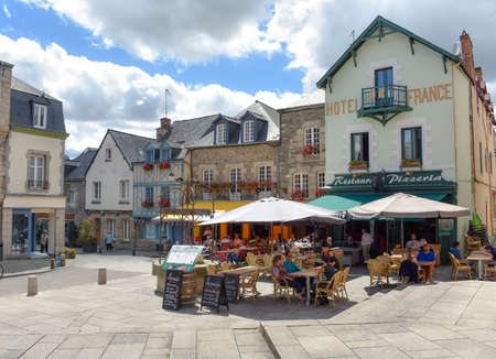 JOSSELIN, FRANCE - JULY 2, 2017: Tourists enjoying on the terraces of a sunny day in Josselin, a French town, located in the Brittany region