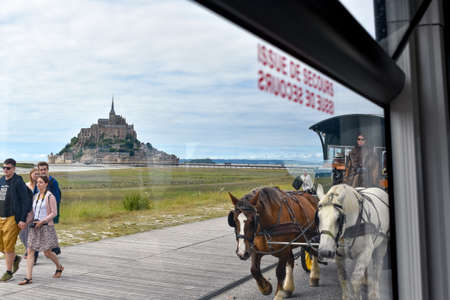 MONT SAINT-MICHEL, FRANCE - JULY 3, 2017: Tourists can choose different means of transportation, walking, bus or horse-drawn carriage. It is not possible to arrive by car to Mont Saint-Michel, one of the most important tourist destinations in French Norma