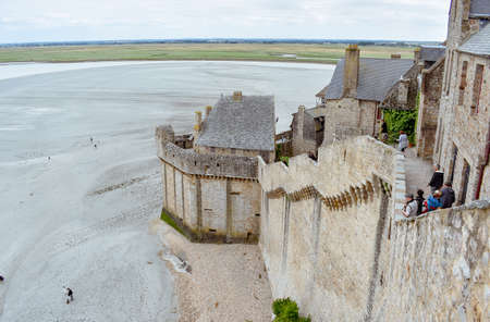 MONT SAINT-MICHEL, FRANCE - JULY 3, 2017: Tourists enjoy the view of the Bay from one of the city walls. Mont Saint-Michel, one of the most important tourist destinations in French Normandy.