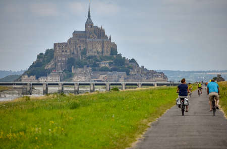 MONT SAINT-MICHEL, FRANCE - JULY 3, 2017: Cyclists go on a summer day to Mont Saint-Michel, one of the most important tourist destinations in French Normandy. Stockfoto - 133917089
