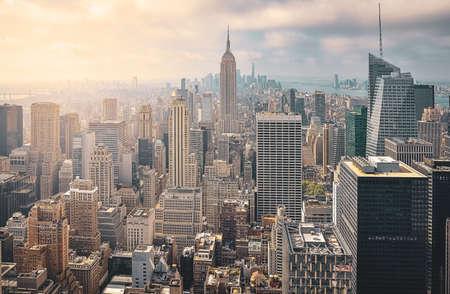 Vue aérienne emblématique de la ville de New York par une journée ensoleillée. Rayons de soleil entre les gratte-ciel et fond nuageux. Concept de voyage. New York, États-Unis.