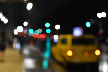 Concept of street and taxi blurred at night with bokeh of lights. NYC, USA.