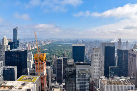 Aerial view of New York with skyscrapers, buildings in construction and central park in the background. Sunny day with some clouds. Concept of travel and construction. NYC, USA.