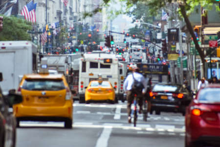 Blurred concept of the frenetic activity of life in New York. Cars, public transportation, bicyclists, pedestrians, buildings, signs and flags. Concept of crowded city and traffic. Manhattan, New York. United States. Stockfoto