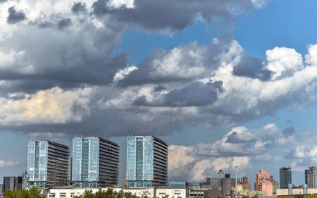 Generic city view with cloudy blue sky. Row of three main buildings in the skyline. Weather and City concept. New York City. United States.