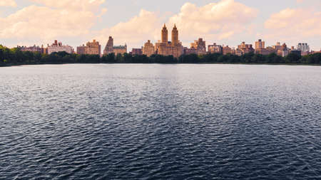 Jacqueline Kennedy Onassis Reservoir lake in Central Park at Sunset. Nyc skyline at background. Travel and City concept. New York City. United States.