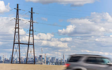 Car leaving NYC. Electrical wiring towers and the city of NYC in the background. New York City. United States.