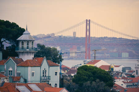 Lisbon panoramic view. Colorful walls of the buildings of Lisbon, with orange roofs and the 25th of April bridge in the background, at sunset. Travel and real estate concept. Lisbon, Portugal. Europe. Stockfoto - 136680969