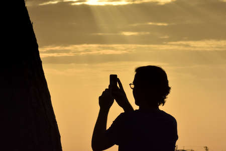 Backlit silhouette of an unrecognizable boy with long hair and glasses, taking a photo with his mobile phone. Lisbon, Portugal. Europe.