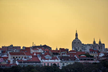Lisbon skyline view. Colorful walls of the buildings of Lisbon, with orange roofs and the Basílica da Estrela at sunset. Travel and real estate concept. Lisbon, Portugal. Europe.