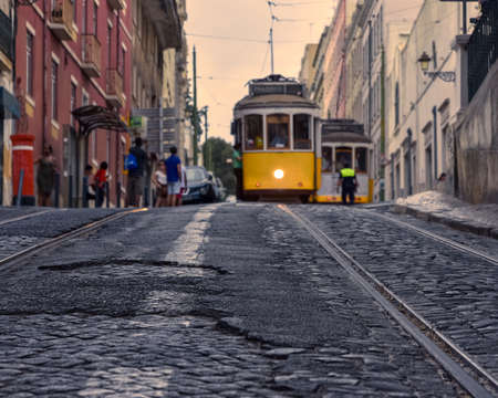 Travel concept of Lisbons famous trams. Focusing on the cobbled streets with the trams in the foreground. In the background, tourists and trams out of focus, in the light of the sunset. Lisbon, Portugal. Europe.