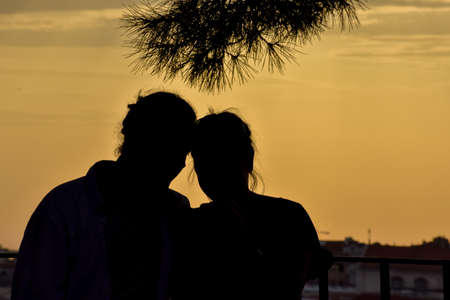 Backlit silhouette of an unrecognizable couple in love. Lisbon, Portugal. Europe.