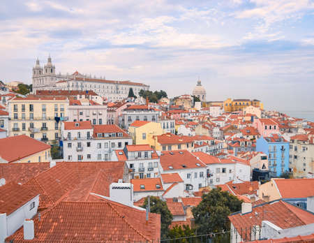 Lisbon panoramic view. Colorful walls of the buildings of Lisbon, with orange roofs and the Church of Sao Vicente of Fora in the background. Sunny dayand blue sky in summer. Travel and real estate concept. Lisbon, Portugal. Europe. Stockfoto