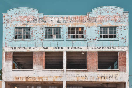 Decay concept. Building in ruins, with chipped paint, showing the good times of the past. Gananoque, Ontario, Canada.
