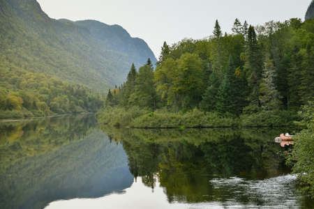 River across the forest in Jacques-Cartier National Park, Canada in a foggy moody sunset. Stock fotó
