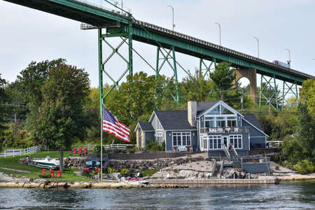 Different buildings in a grassy area on the coast of a lake during daytime, and surrounded by trees. United States flag, and boat cottage. Real State concept. Thousands Islands. Ontario, CanadaUnited States. Stockfoto