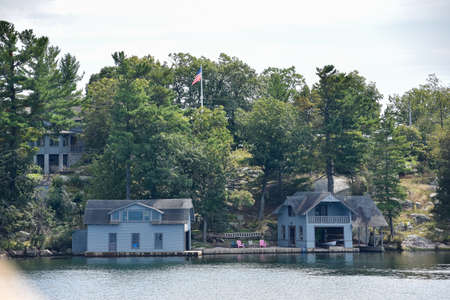 A lot of different buildings in a rocky area on the coast of a lake during daytime, and surrounded by trees. Real State concept. Thousands Islands. Ontario, Canada