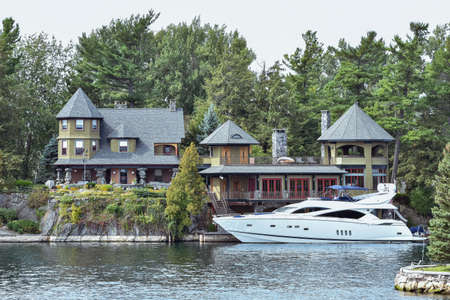 Building in a grassy area on the coast of a lake during daytime, and surrounded by trees. Yacht parked in the lakeside harbor. Real state and luxury concept. Thousands Islands. Ontario, Canada