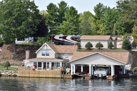 A lot of different buildings and boat cottage in a grassy area on the coast of a lake during daytime, and surrounded by trees. Real State concept. Thousands Islands. Ontario, Canada. Stockfoto