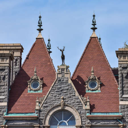 Detail of two equal red brick towers, in a stone building. In the middle, a decorative deer statue. Architecture concept A thousand islands, Ontario. Canada.