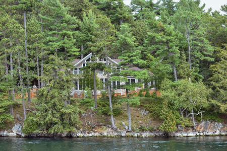 Isolated cottage in a rocky area on the coast of a lake during daytime, and surrounded by trees. Real State concept. Thousands Islands. Ontario, Canada.