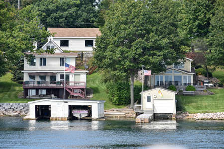 Different buildings in a grassy area on the coast of a lake during daytime, and surrounded by trees. United States flags, and boat cottage. Real State concept. Thousands Islands. Ontario, CanadaUnited States. Stockfoto