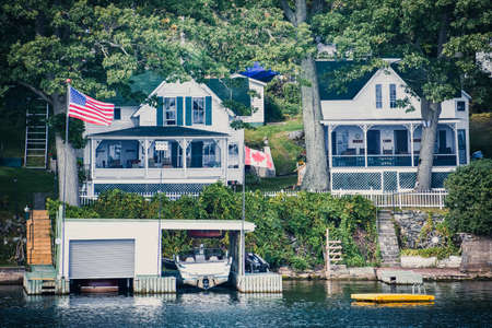 Different buildings in a grassy area on the coast of a lake during daytime, and surrounded by trees. Canadian and United States flags, and boat cottage. Real State concept. Thousands Islands. Ontario, CanadaUnited States